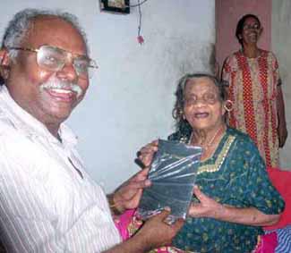 Eliyamma receives Bible from Paul Ciniraj