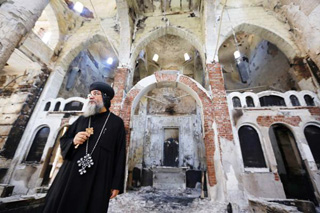 Bishop Makarios stands in Evangelical Church of Minya after its destruction by Islamists