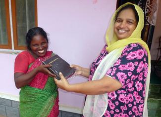 Usha (left) receives Bible from Mercy Ciniraj