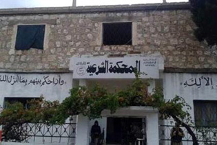 """A sharia court set up in a building in Kansabba, Syria. The writing on the left reads: """"Judge people according to the words of Allah."""" Centre: """"Sharia Court."""" Right: """"There is no God but Allah."""" Photo courtesy of Nuri Kino"""