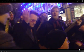 Bono lifts hand in reverence
