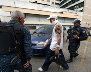 A wounded gang member is apprehended by police officers in Tegucigalpa, Honduras. Over 4,700 gang members are youth or children.