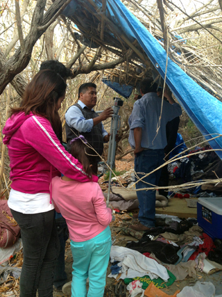 Gonzolo (center) ministers at homeless camp in riverbed