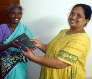 Nagamma (Maria) receives Bible from Mercy Ciniraj