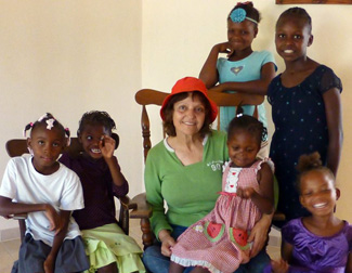 Norma with children who are provided an education through Restore a Child
