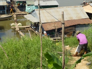 A Vietnamese immigrant hauls pig feed down to his floating house along the Tonle Sap River
