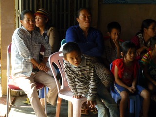 Children and their parents wait and watch in the same room where Dr. Yamamoto works