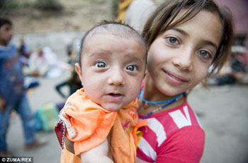 Yazidi girl holds brother, waits for bread in Dohuk refugee camp