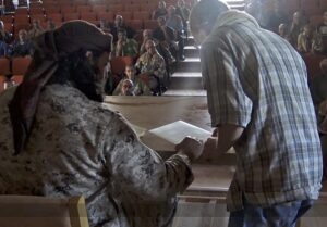 Islamic State member gives Dhimma (second-class) contracts for Christians to sign. (photo: Islamic State)