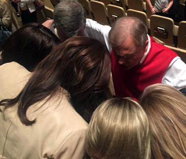 Ed Young (red sweater vest) prays with Caitlyn Jenner (tan coat)