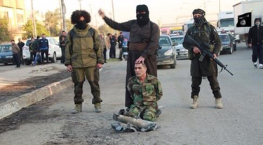ISIS fighter prepares to behead a captured Peshmerga fighter in Mosul