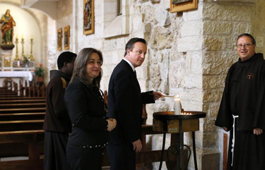 British Prime Minister David Cameron (C) lights a candle as he visits the Church of the Nativity in 2014. (REUTERS/Thomas Coex/Pool)