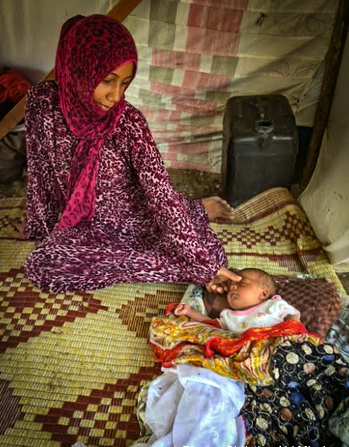 Syrian refugee woman and child from Aleppo, Syria at a makeshift tent camp in Turkey (Christian Aid Mission)