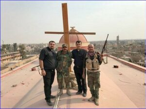 Father Ammar, another priest and two soldiers stand by a newly erected cross on the roof of Tahira church (church of the Immaculate, Syriac Catholic) in Qaraqosh, a Christian village liberated from IS.           (World Watch Monitor)